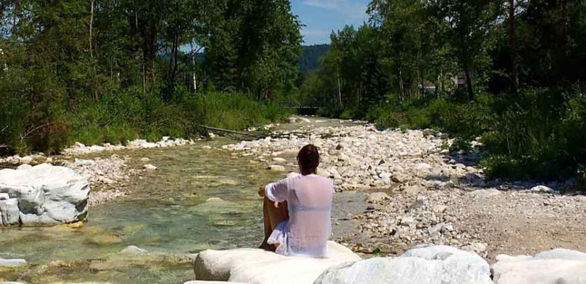 woman with her back to the camera looking downstream at a river with many white pebbles and rocks.