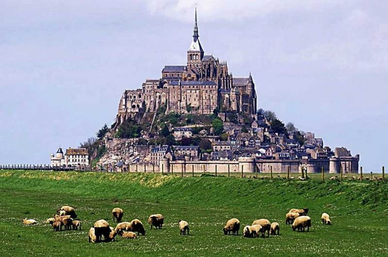 a large monastery on top of the small island that is St-Mont-Michel