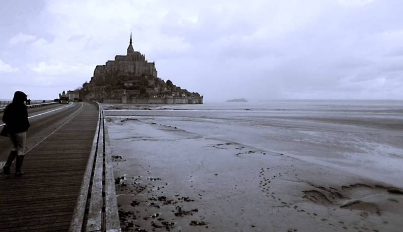 Mont st Michel in the background. The tide is out and there is a vast expanse of sand to the right of the photo. A long wooden bridge leads towards the island with a high steeple at the peak of the monastery.