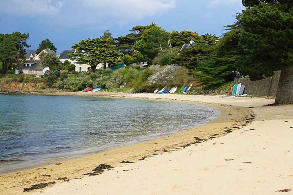 Small winding stretch of beach with boogy boards leaning against a stone wall