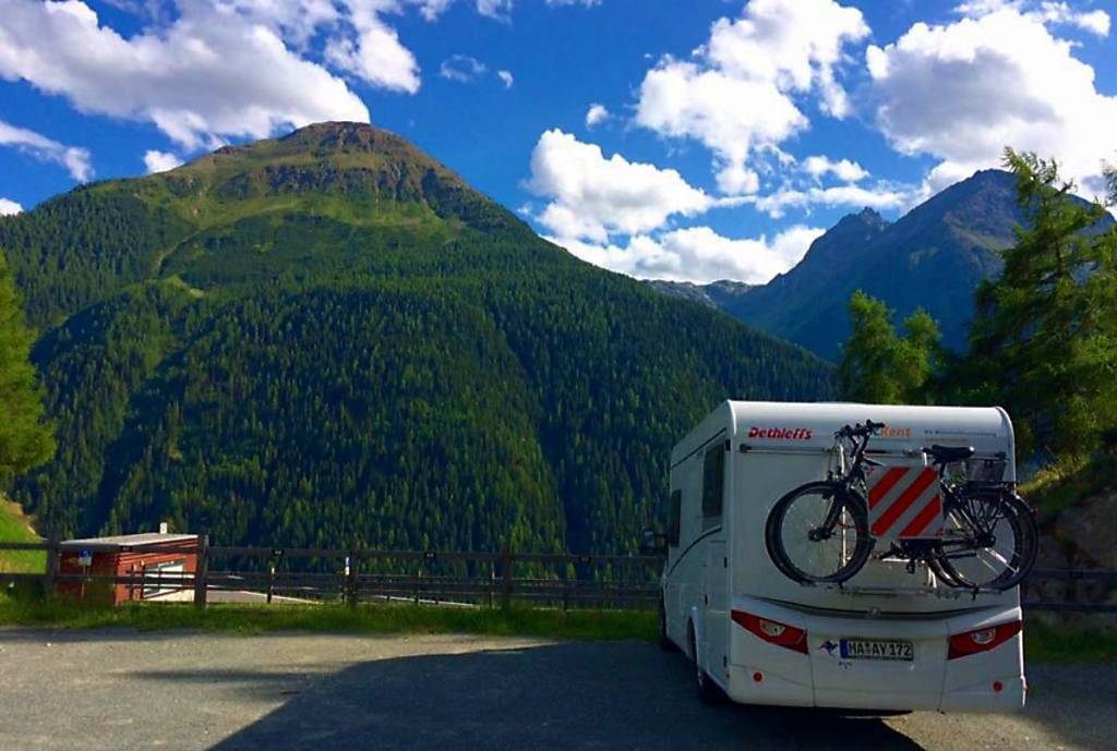 high green mountain in the background - white motorhome parked to the right with two bikes on the back and a red and white striped sign