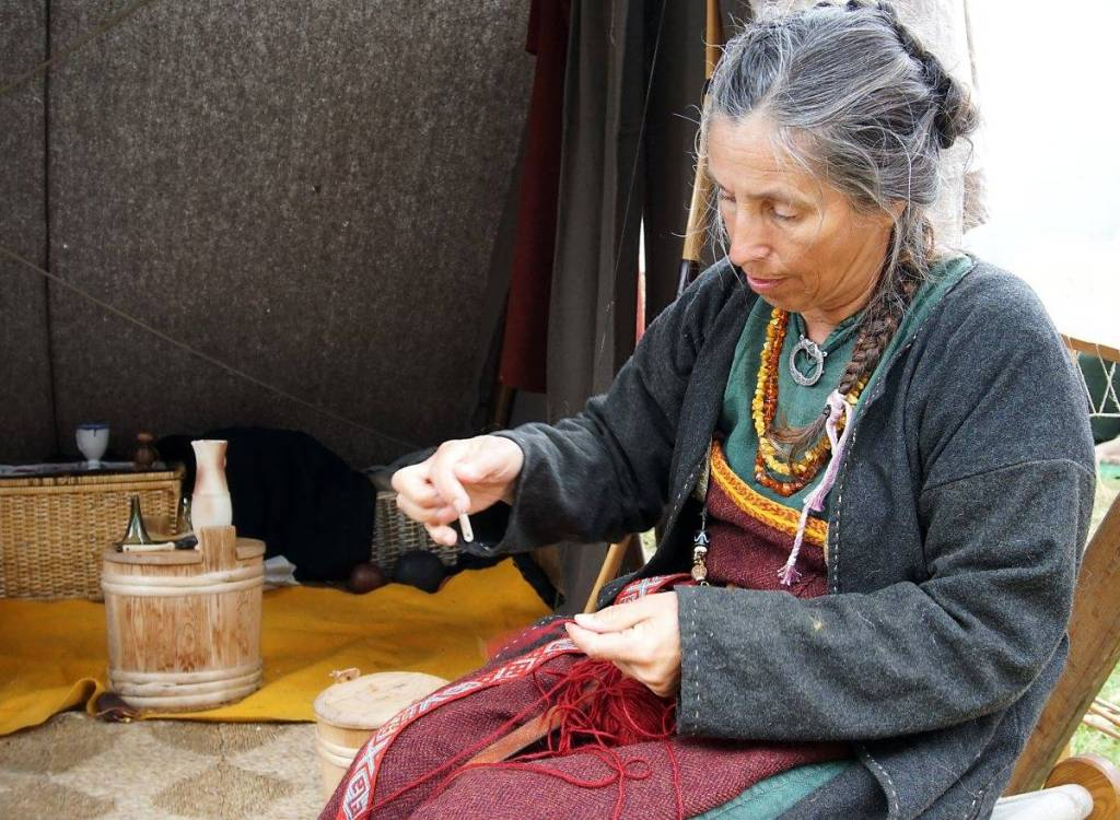 A woman dressed as a viking spinning yarn