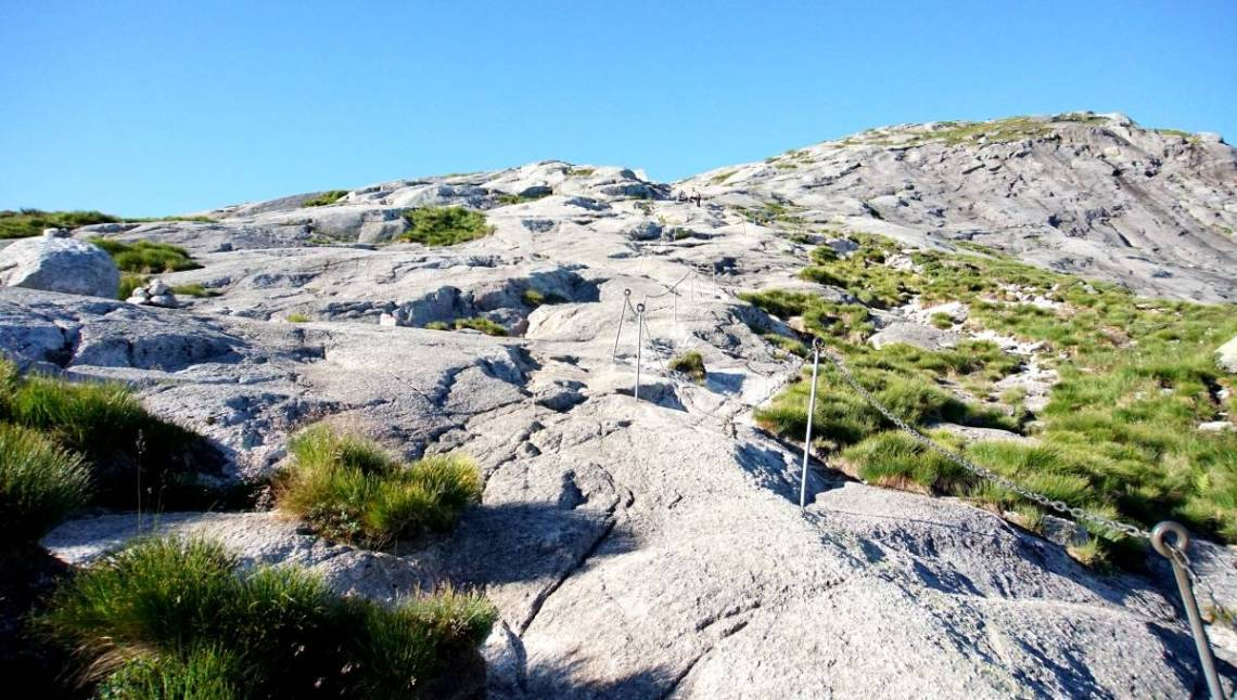 Asteep grey granite climb at the start of the Kjeragbolten hike. Silver metal poles with chains connected help you climb the incline. Some rough grass patches to the side.