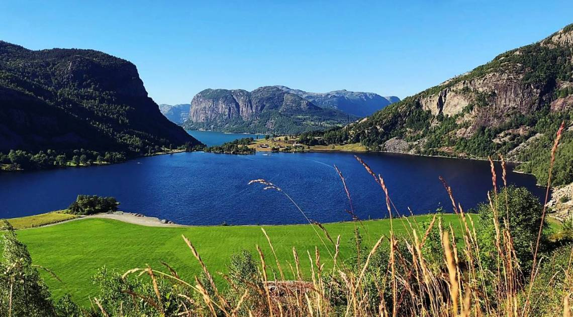 Deep blue lake surrounded by mountains, with grass in the foreground.