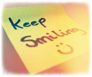 A yellow post it note with Keep smiling written on it
