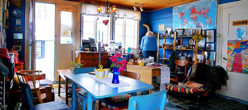 The inside of the cafe majorstuen, a blue table and chairs is in the foreground. The entrance and window are in the background. A world map is on the wall.