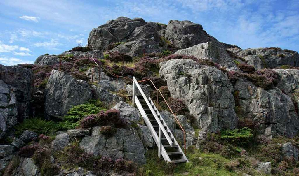 A clump of rock with a wooden staircase leading up the side of the rock.