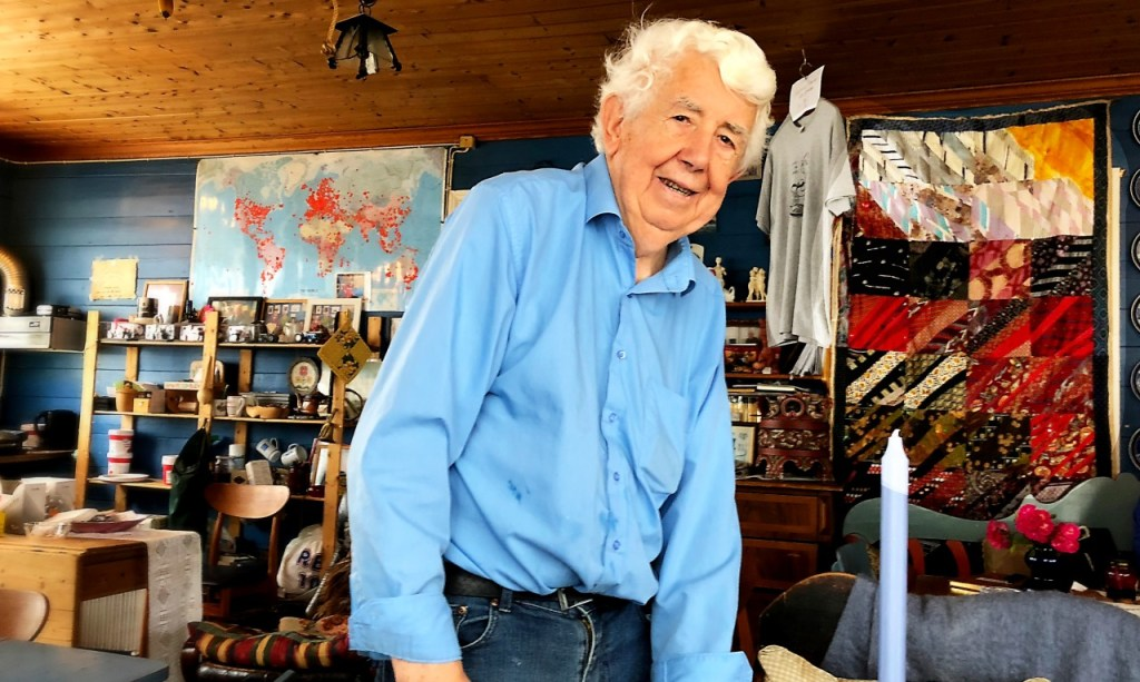 Johannes, a white haired man with a blue shirt. In the background is a multi-coloured quilt made of many ties.