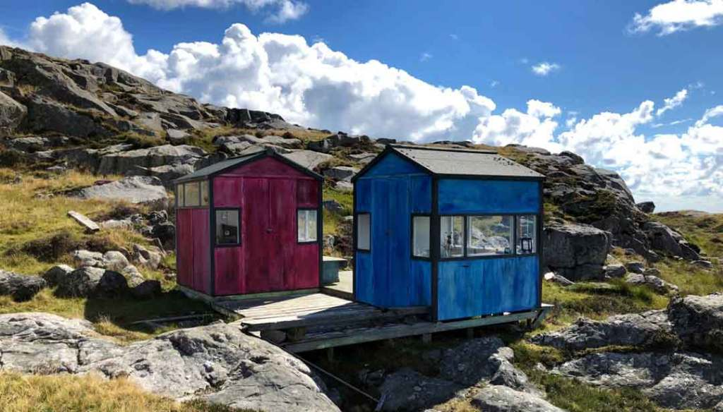 Two smal huts, one pink, one blue on the craggy landscape of rocks and grass