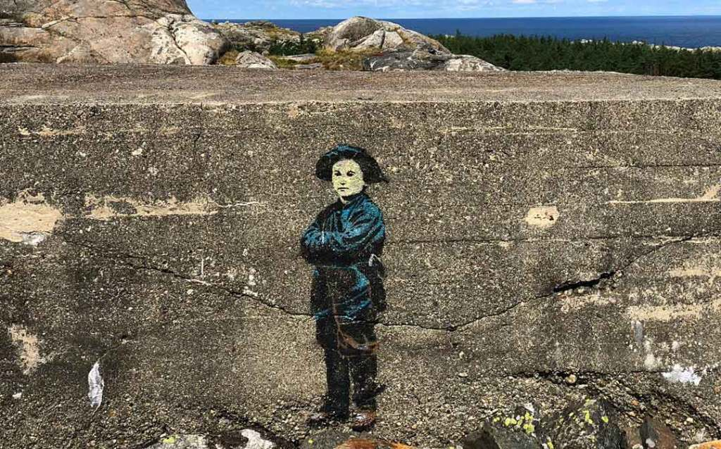 A painting of a boy wearing blue clothing and a blue hat on the side of a concrete block.