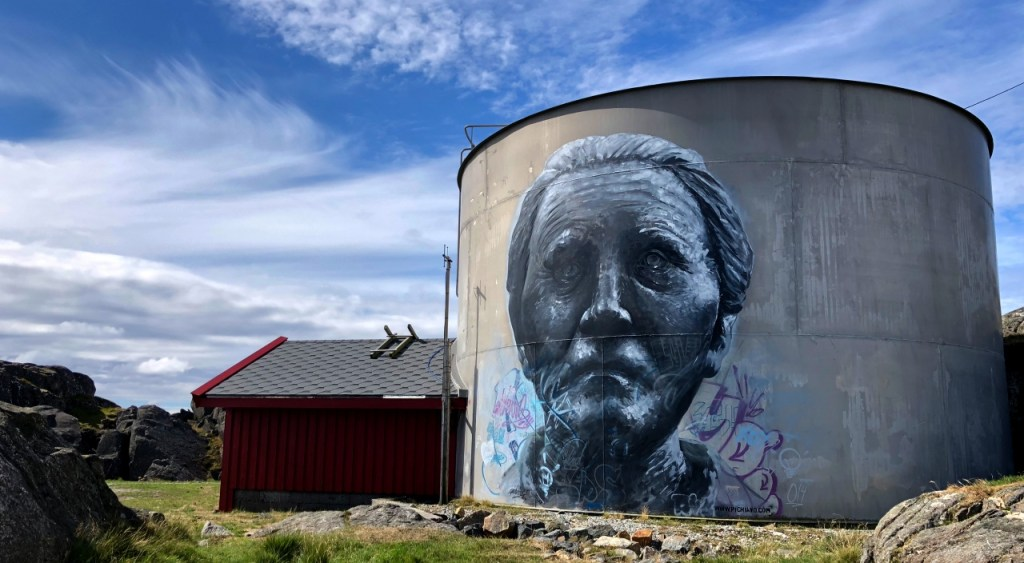 A large water tank with a mural of an old womans face on it .