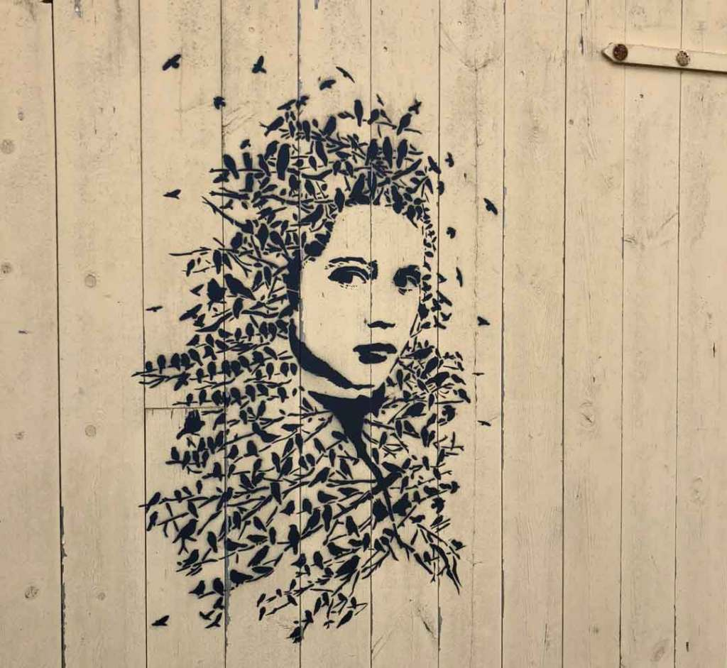 A wooden door with a girls head painted on. Her hair is made up of loads of tiny birds