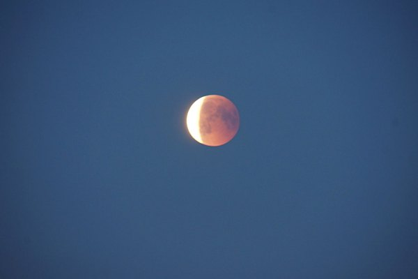 Moon just coming out of earths shadow , so light on left side and pinky red colour on right