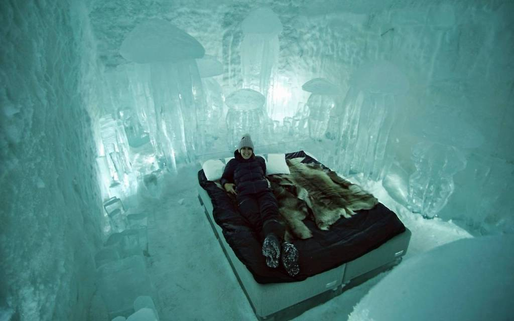 Our room in the 365 Ice Hotel -Michelle wearing pink beanie and black heavy snow clothing.She is lying on the ice bed. All around are large jellyfish carved out of the ice.