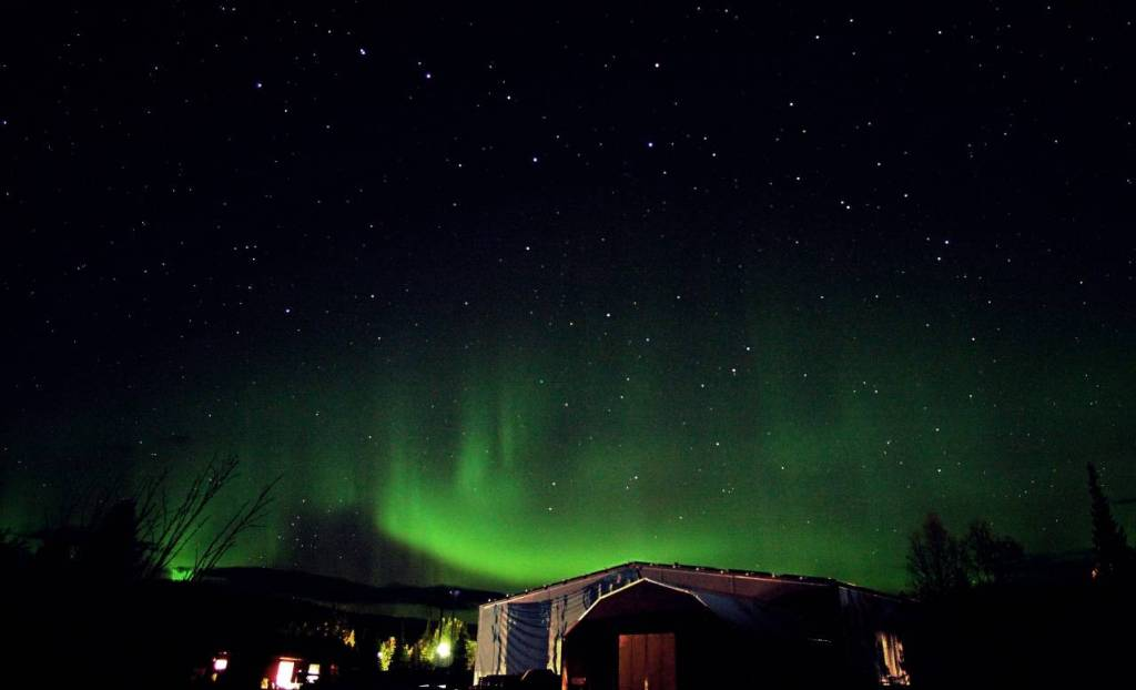 Green swirls of northern lights above the ice Hotel with a black sky and stars