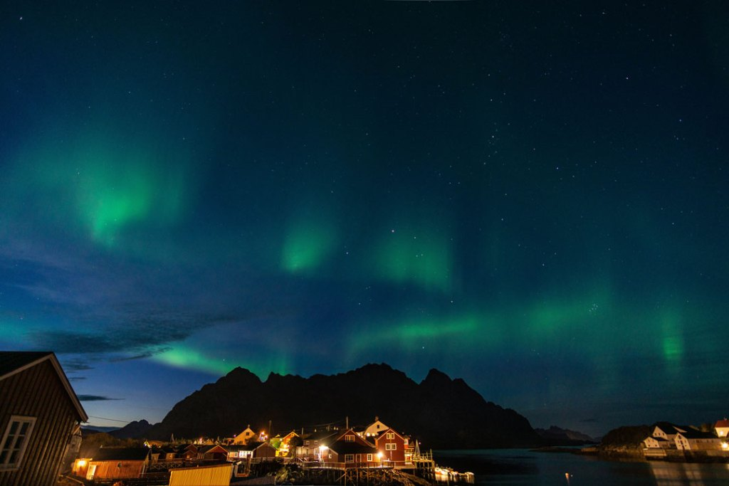 Green curtains of northern lights with a dark mountain backdrop