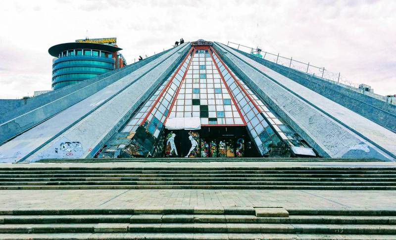 A large pyramid shaped building with a central panel of glass.