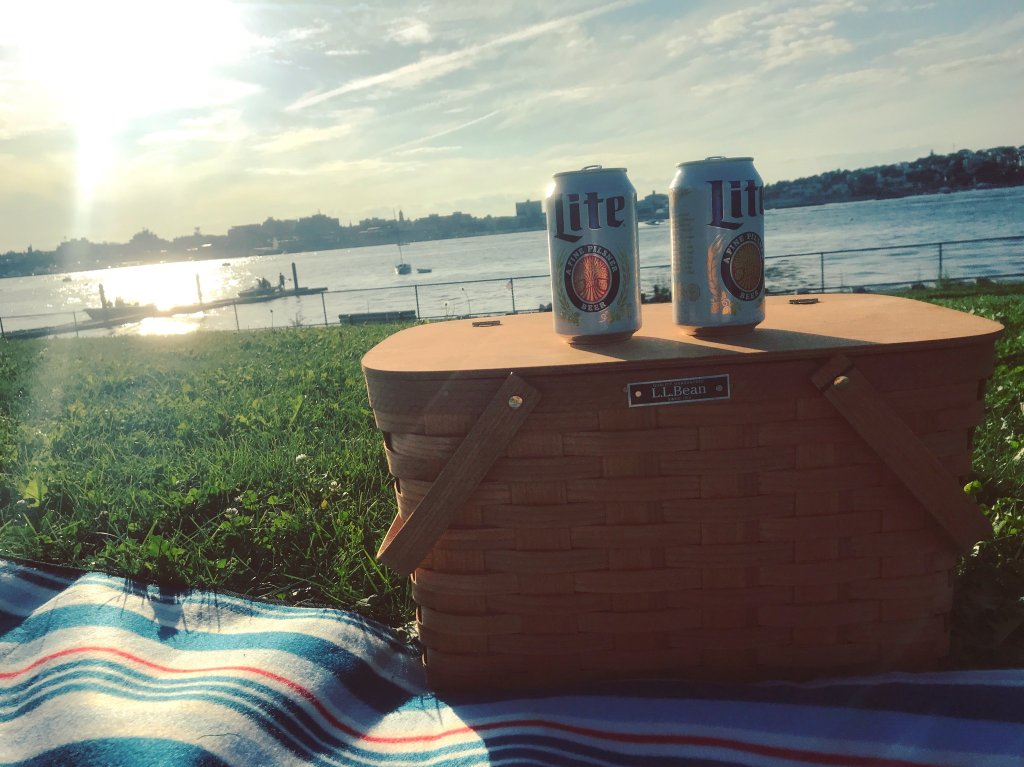 A picnic basket on a picnic blanket with 2 beers sitting on top. A view of the ocean and the city is in the background - a perfect view for a perfect picnic.