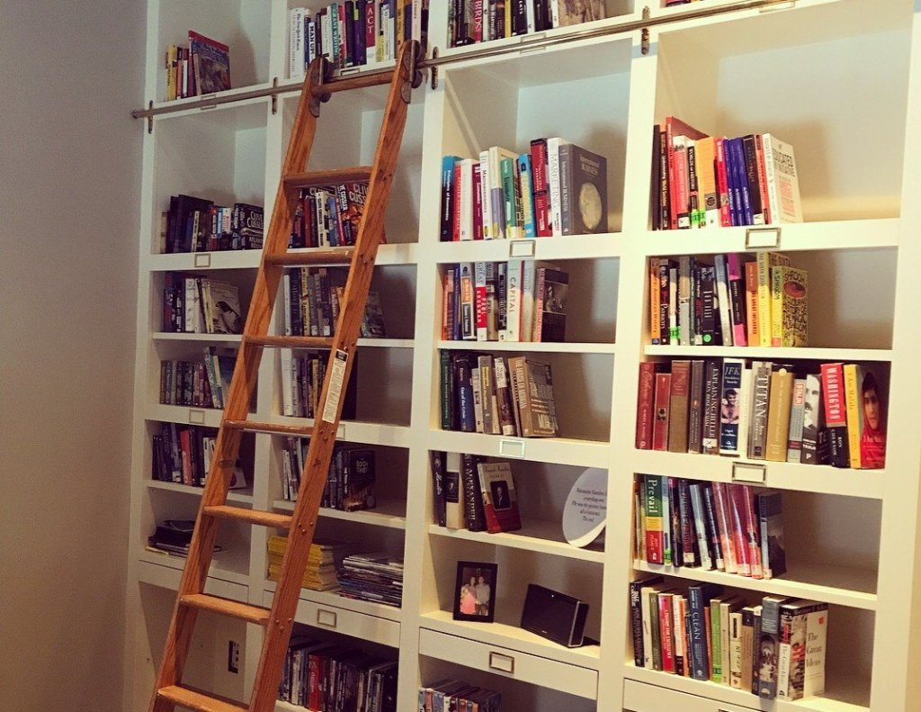 Book shelves filled with books and a ladder leading to the top shelf.