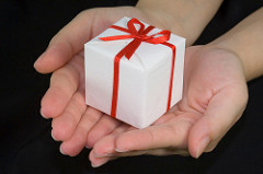 pair of hands lovingly presenting a gift