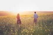 couple walking a field watching sunset