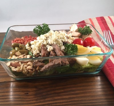 clear, glass, rectangular dish filled with romaine lettuce, topped with steak strips, blue cheese crumbles, whole pecans, bacon bits, sliced cherry tomatoes, sliced fresh mushrooms, green olives, and a hard boiled egg sliced in half.