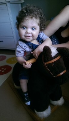 Loving his first ride on his rocking horse