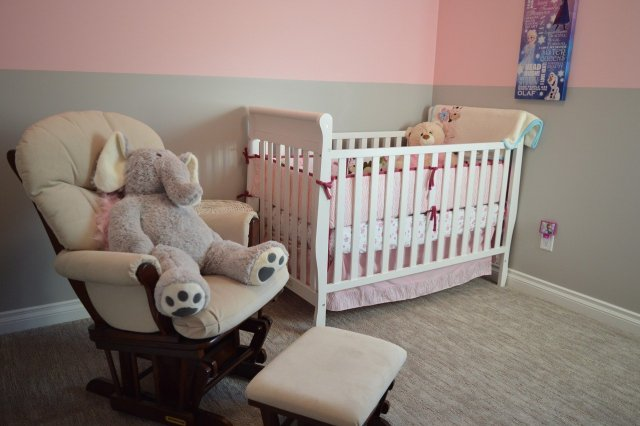 A nursery with a crib and rocker chair.