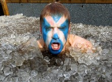 Man with Scottish flag painted on face popping out of an ice bath