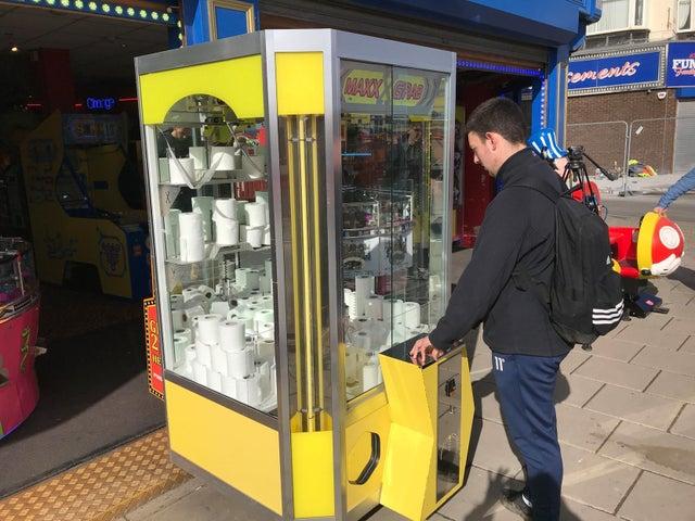 An man playing an arcade grabber machine full of toilet rolls