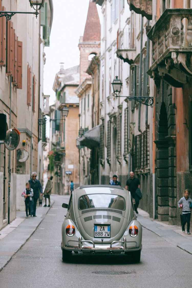 retro car driving along narrow road in historic city