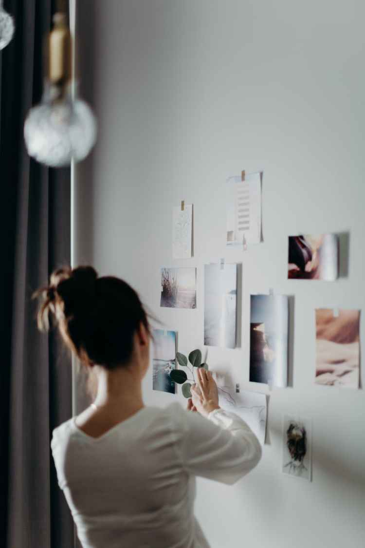woman putting photos on wall
