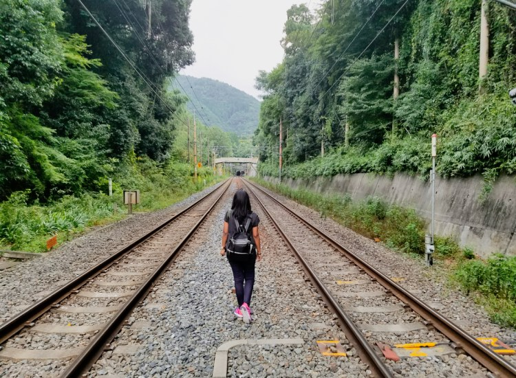 girl with a black backpack walking on a railway track