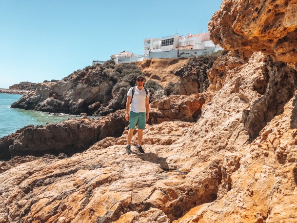 Man standing on rock formations in Albufeira