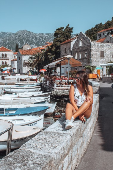 Girl sitting on hedge in Perast, Montenegro