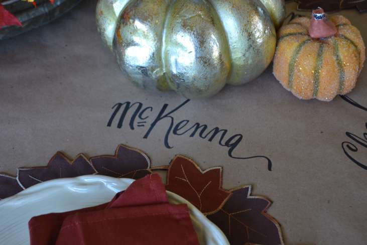 Using brown craft wrapping paper as a runner and hand lettering place settings and messages creates a sweet and cozy table for Fall.