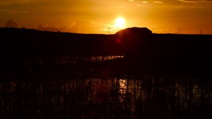 The setting sun reflecting on a tarn fast drying up.