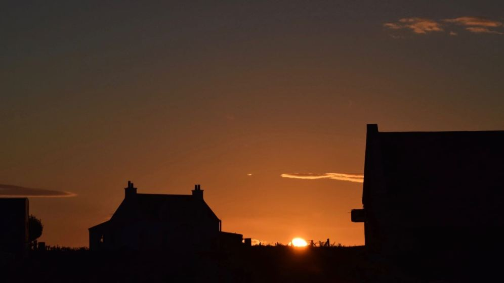 The sun drops down behind the Scarinish skyline