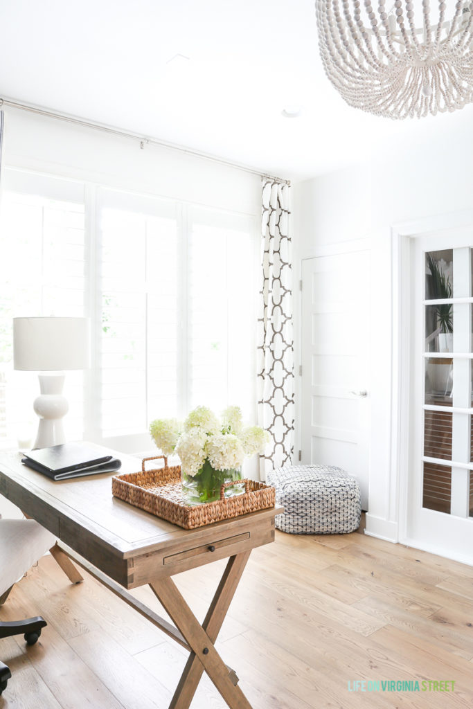 A light wood office desk, with white flowers on it, and new hardwood floors in office.