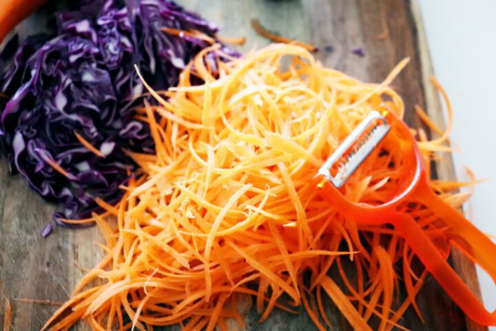 A cutting board with shredded carrots, red cabbage and peeler