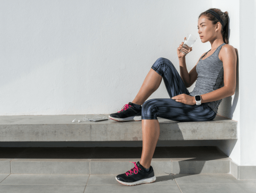 Woman in activewear drinking water
