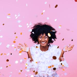 Woman celebrating Ibotta's $500 Million Moment with Confetti