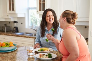 Two Women Eating Healthy Meal In Kitchen