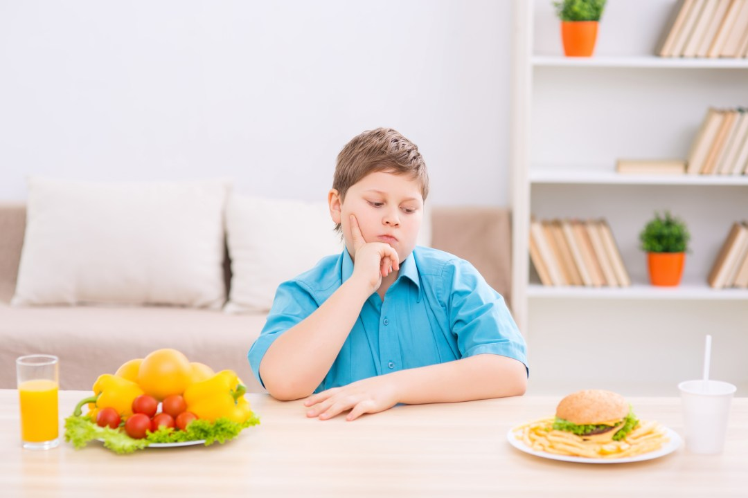 Boy sitting at table deciding between two plates - one with fruit and one with a hamburger