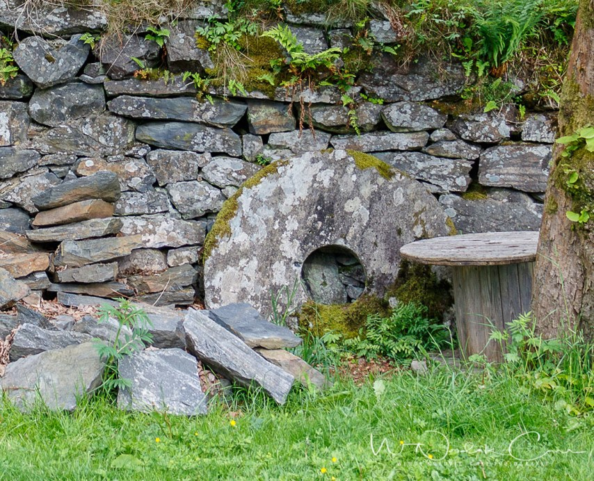 A historic stone mill wheel leans against a granite rock wall at the museum.