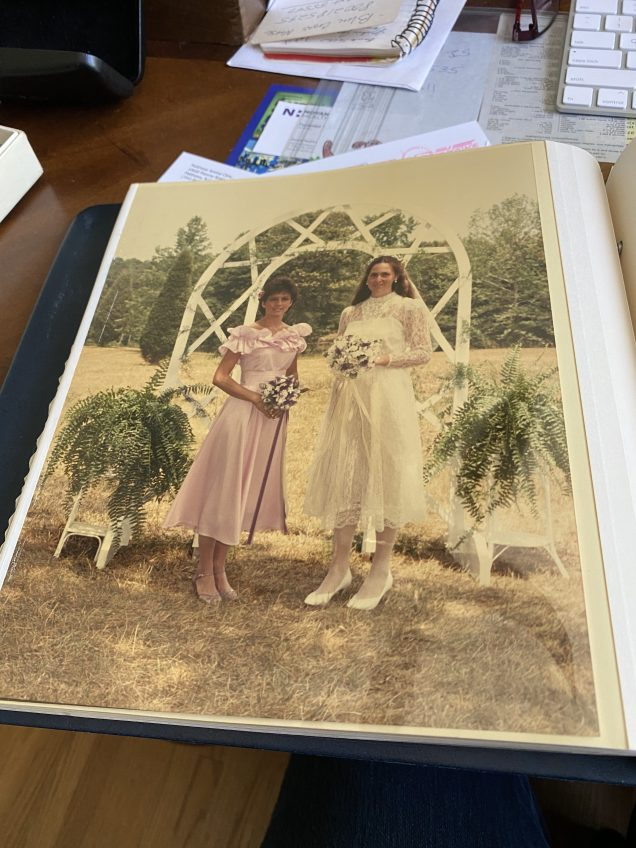 Bride and bridesmaid in old album in yellow sleeve