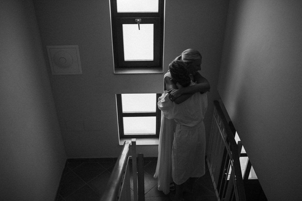 bride and bridesmaid sister hugging when getting ready on her wedding day