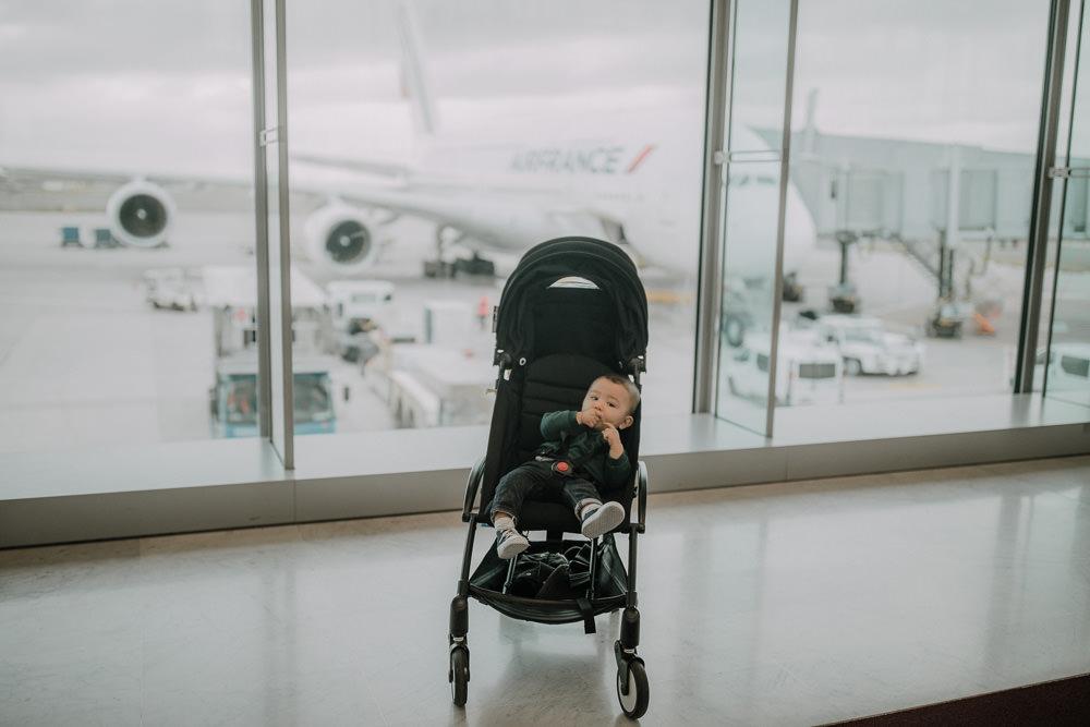 Baby in front of Air France A380 plane in a Babyzen Yoyo pram