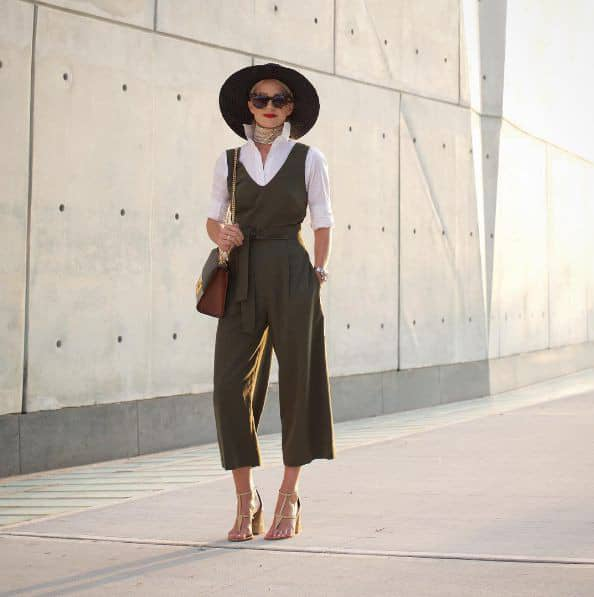 lady wearing jumpsuit on white shirt, hat and glasses
