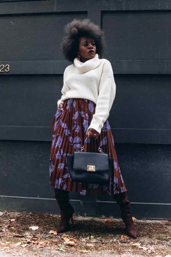 lady wearing white polo neck sweater with skirt and knee-high boots